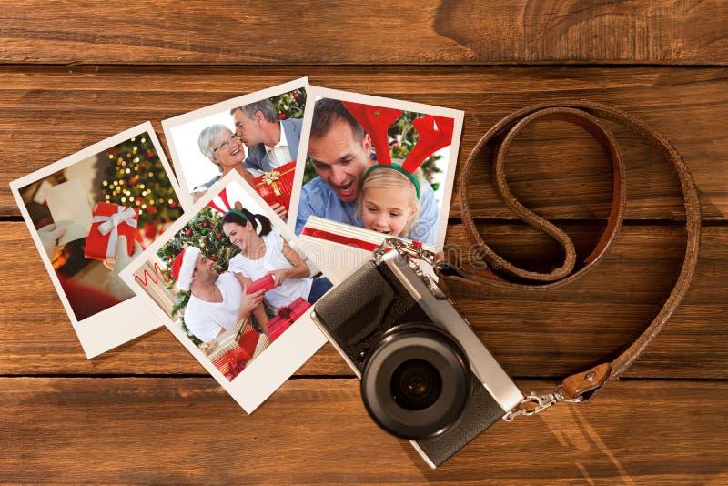 Sammansatt bild av den höga mannen som ger en kyss och en julgåva till hans fru royaltyfri fotografi