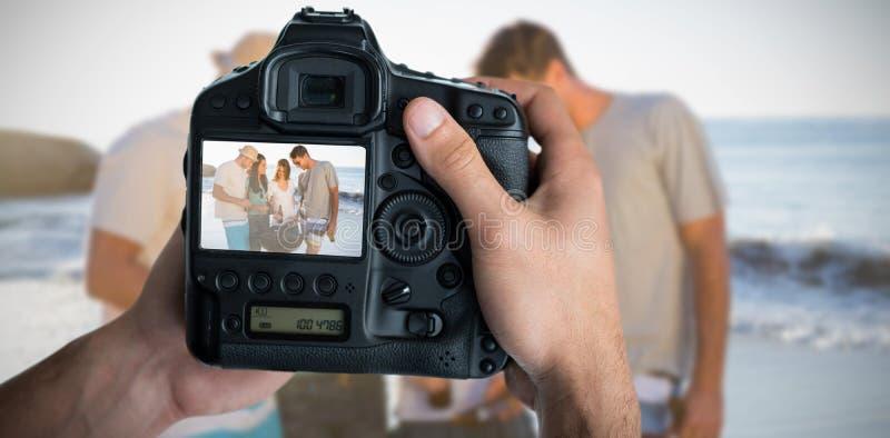 Sammansatt bild av den kantjusterade bilden av händer som rymmer kameran royaltyfria foton