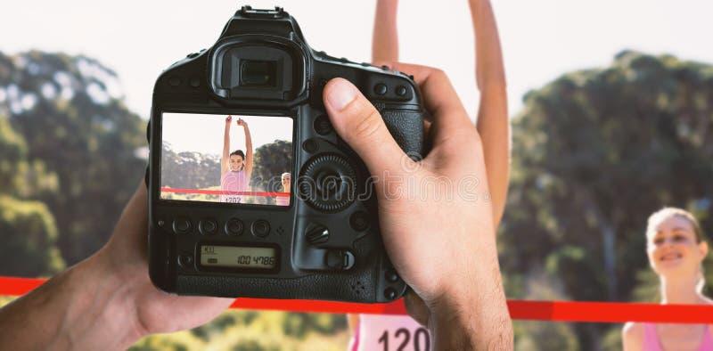 Sammansatt bild av den kantjusterade bilden av händer som rymmer kameran arkivfoton