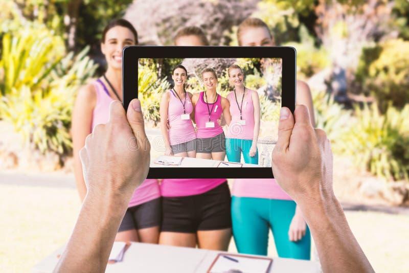 Sammansatt bild av den kantjusterade handen som rymmer den digitala minnestavlan arkivfoton
