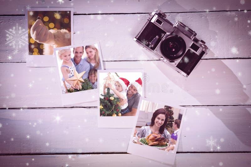 Sammansatt bild av den lyckliga fadern som hjälper hans son att sätta en ängel på julträdet arkivfoton