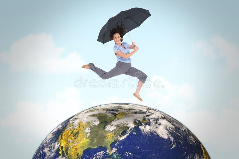 Sammansatt bild av den lyckliga flotta affärskvinnabanhoppningen, medan rymma paraplyet arkivfoton