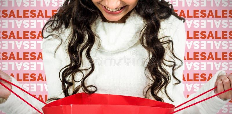Sammansatt bild av den lyckliga kvinnan med julhatten som ser i röd shoppingpåse royaltyfri foto