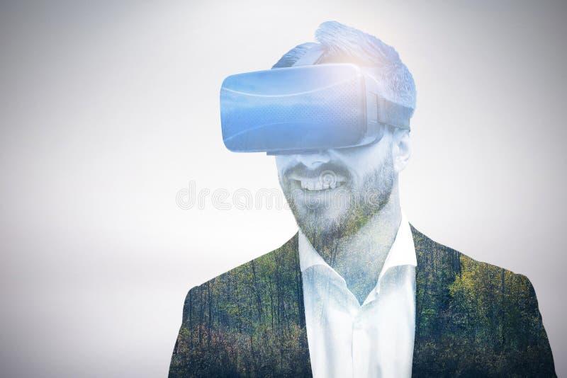 Sammansatt bild av den lyckliga unga affärsmannen som använder virtuell verklighetexponeringsglas arkivbilder