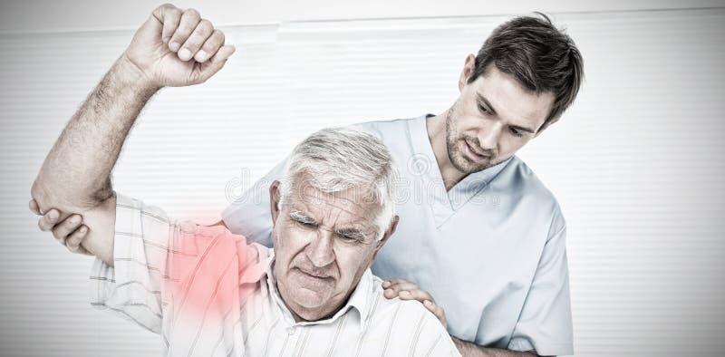 Sammansatt bild av den manliga fysioterapeuten som hjälper den höga mannen för att lyfta handen royaltyfri bild