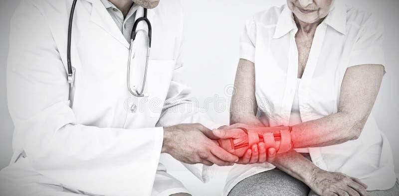 Sammansatt bild av den manliga fysioterapeuten som undersöker höga en kvinnas handled arkivfoto