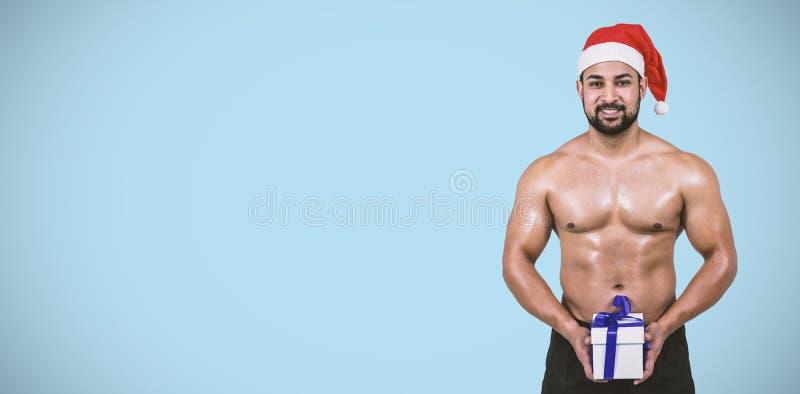 Sammansatt bild av den muskulösa mannen i den santa hatten royaltyfria bilder