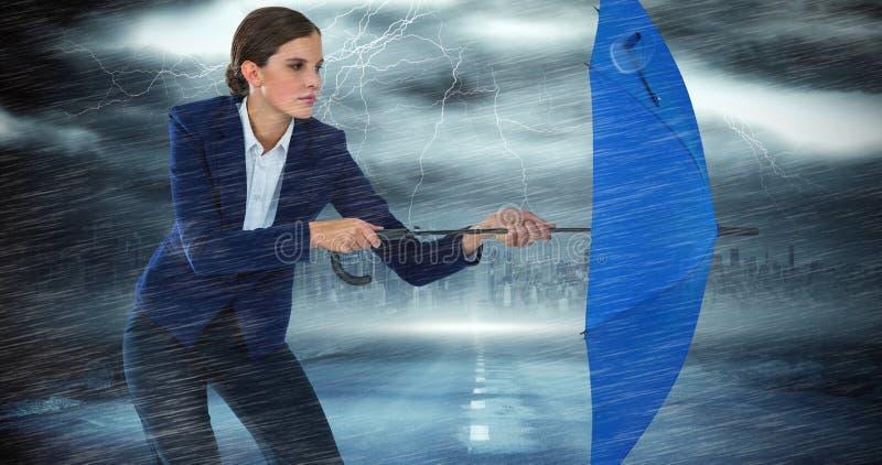 Sammansatt bild av den säkra affärskvinnan som försvarar med det blåa paraplyet arkivfoton