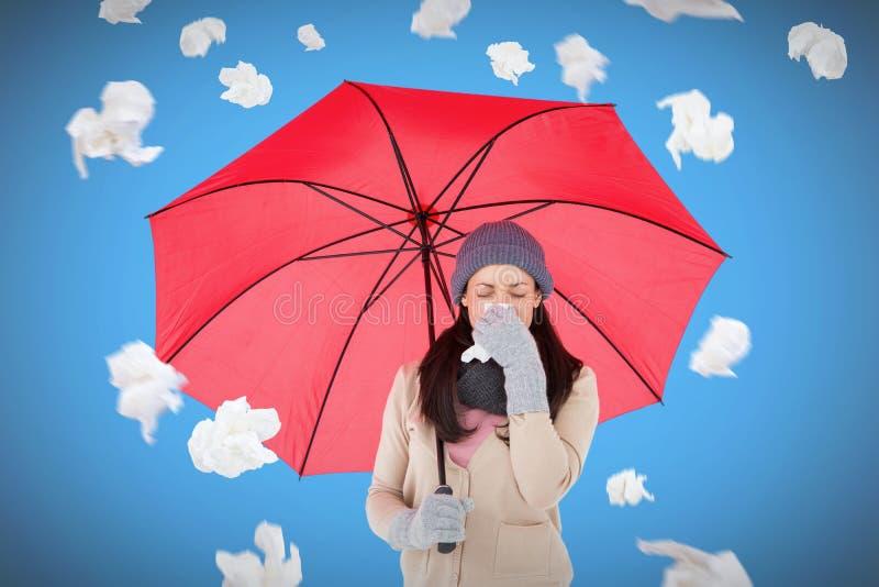 Sammansatt bild av den sjuka brunetten som blåser hennes näsa, medan rymma ett paraply royaltyfri foto