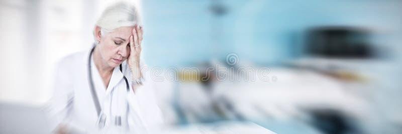Sammansatt bild av den trötta kvinnliga doktorn som använder bärbara datorn på skrivbordet fotografering för bildbyråer