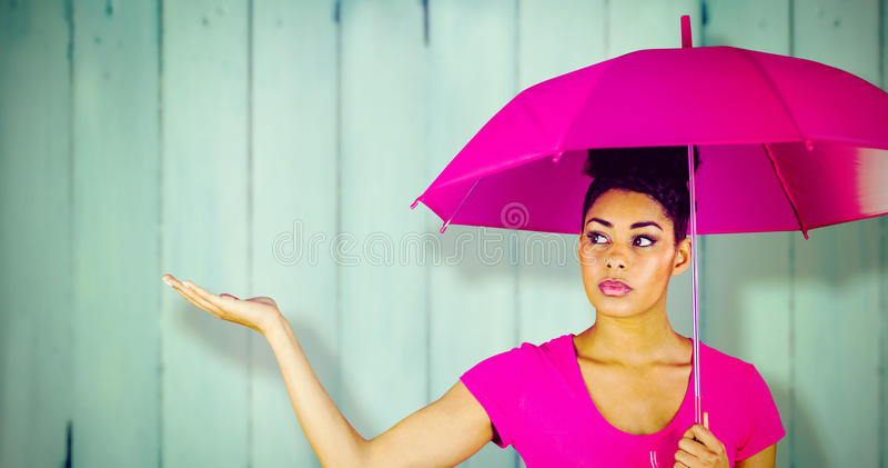 Sammansatt bild av den unga kvinnan som bär det rosa paraplyet royaltyfria bilder