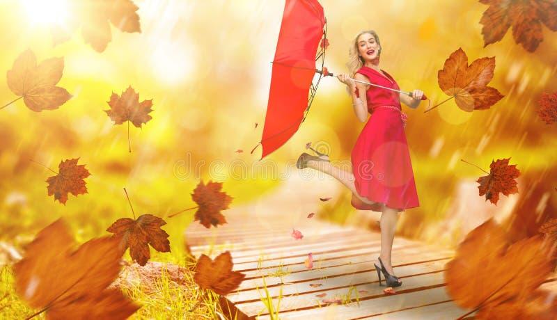 Sammansatt bild av det eleganta blonda hållande paraplyet arkivfoton