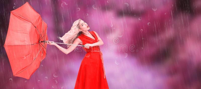 Sammansatt bild av det eleganta blonda hållande paraplyet royaltyfri fotografi