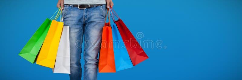 Sammansatt bild av det låga avsnittet av mannen som bär den färgrika shoppingpåsen arkivfoton