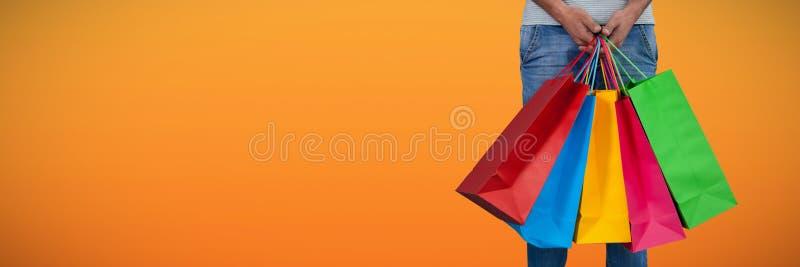 Sammansatt bild av det låga avsnittet av mannen som bär färgrikt anseende för shoppingpåse mot den vita backgrouen arkivbild