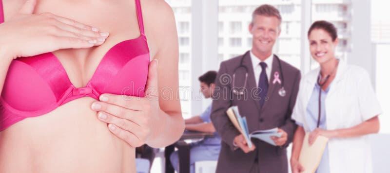 Sammansatt bild av det mitt- avsnittet av kvinnan i rosa behå som kontrollerar bröstet för cancermedvetenhet royaltyfri fotografi