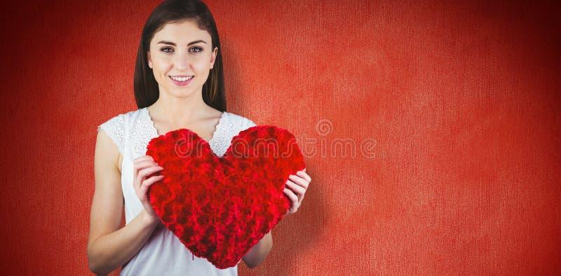 Sammansatt bild av för hjärtaform för kvinna den hållande kudden royaltyfri foto