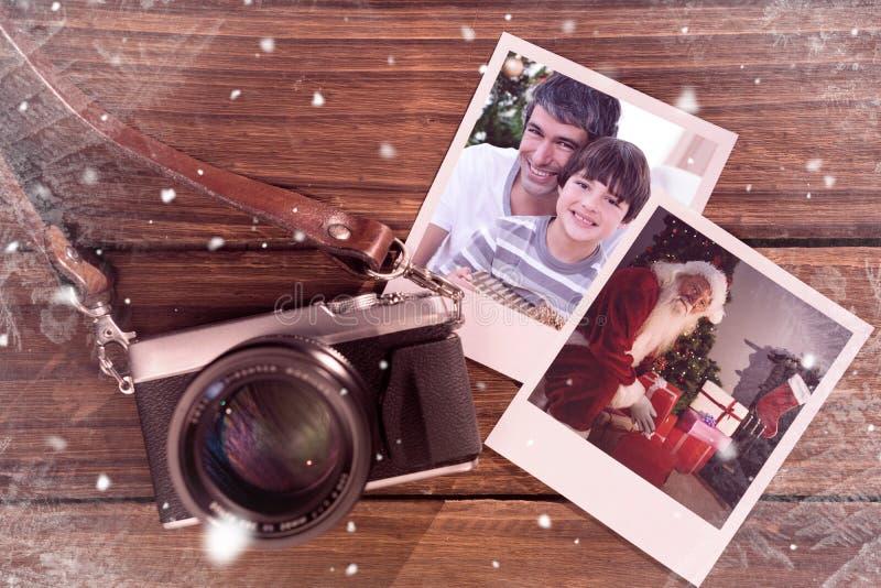 Sammansatt bild av fadern och sonen som rymmer en julgåva royaltyfri bild