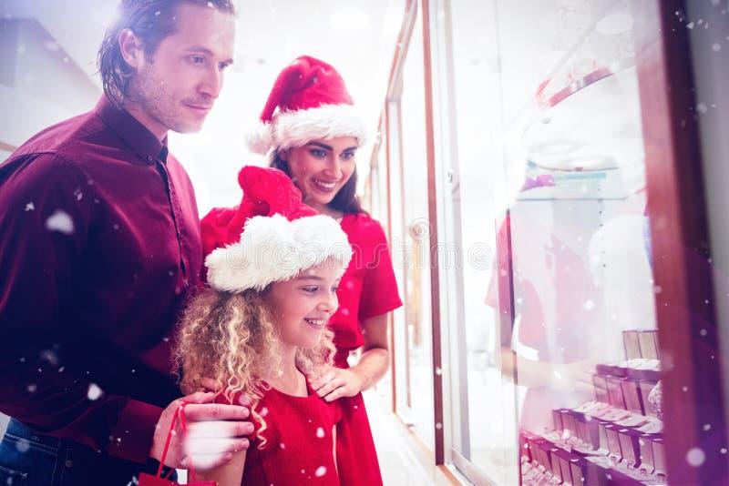 Sammansatt bild av familjen i juldress som ser smyckenskärm arkivfoton