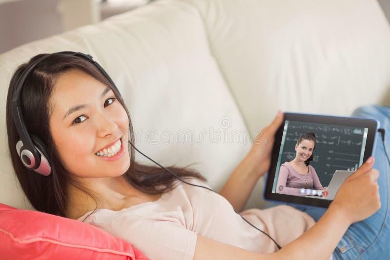 Sammansatt bild av flickan som använder hennes minnestavlaPC på soffan och lyssnar till musik som ler på kameran arkivfoton
