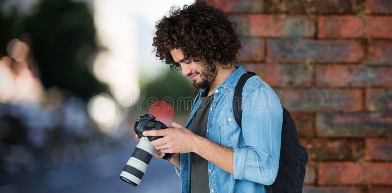 Sammansatt bild av fungerande kameran för ung manlig fotograf arkivbilder