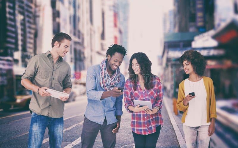 Sammansatt bild av fyra stilfulla vänner som ser minnestavla- och innehavtelefoner royaltyfria bilder
