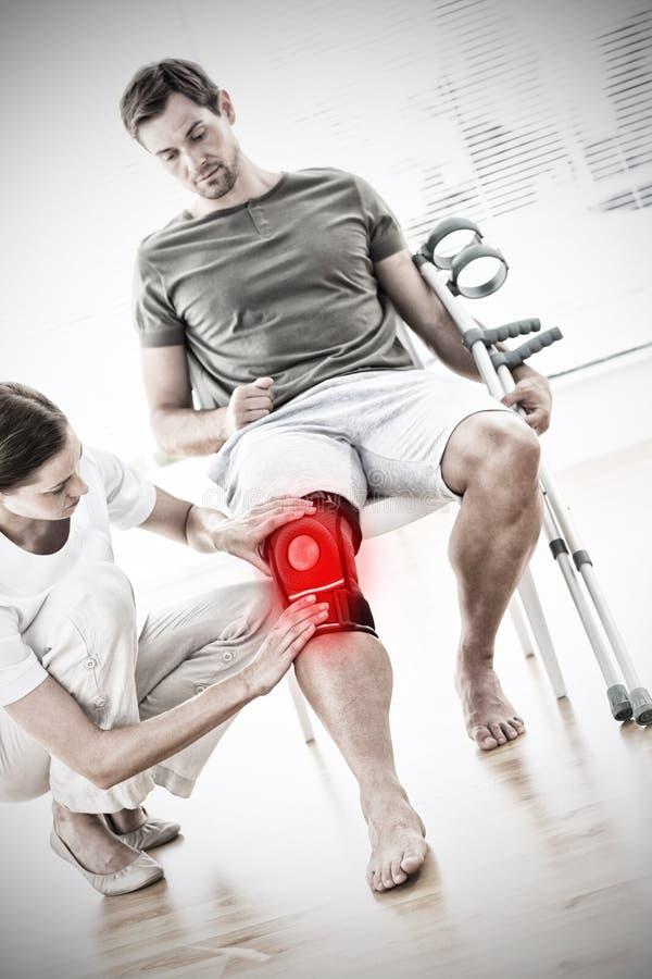 Sammansatt bild av fysioterapeuten som kontrollerar mannen med kryckor royaltyfria bilder