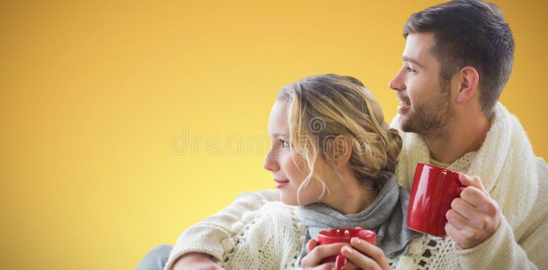 Sammansatt bild av gladlynta par i koppar för vinterklädinnehav mot fönster royaltyfri fotografi