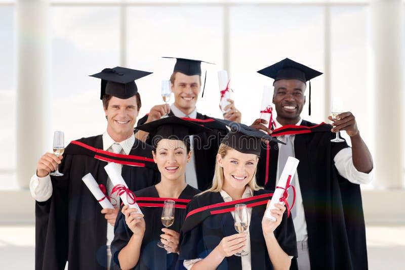 Sammansatt bild av grupp människor som avlägger examen från högskolan royaltyfria bilder