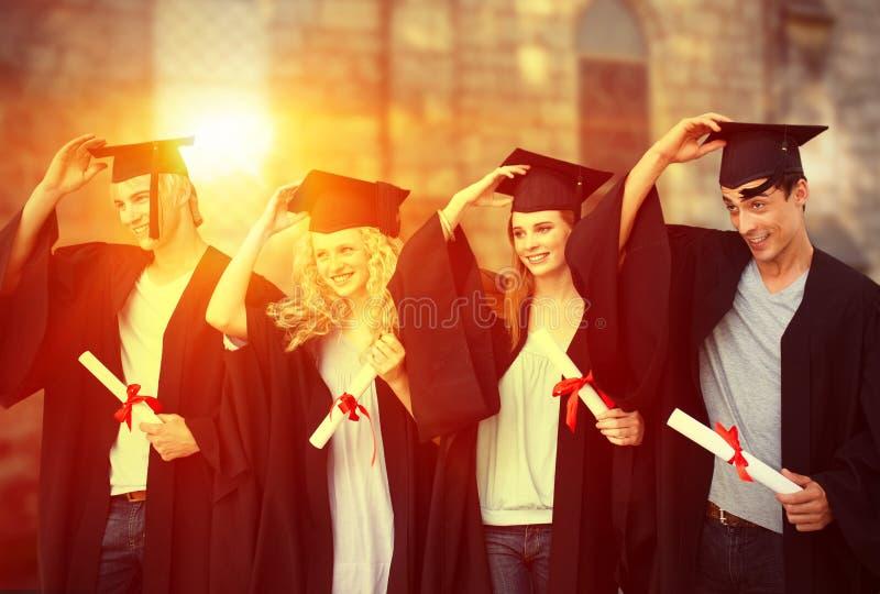Sammansatt bild av gruppen av tonåringar som firar efter avläggande av examen royaltyfri foto