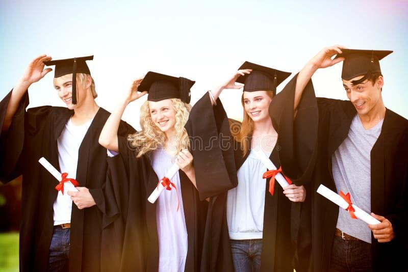 Sammansatt bild av gruppen av tonåringar som firar efter avläggande av examen royaltyfria bilder
