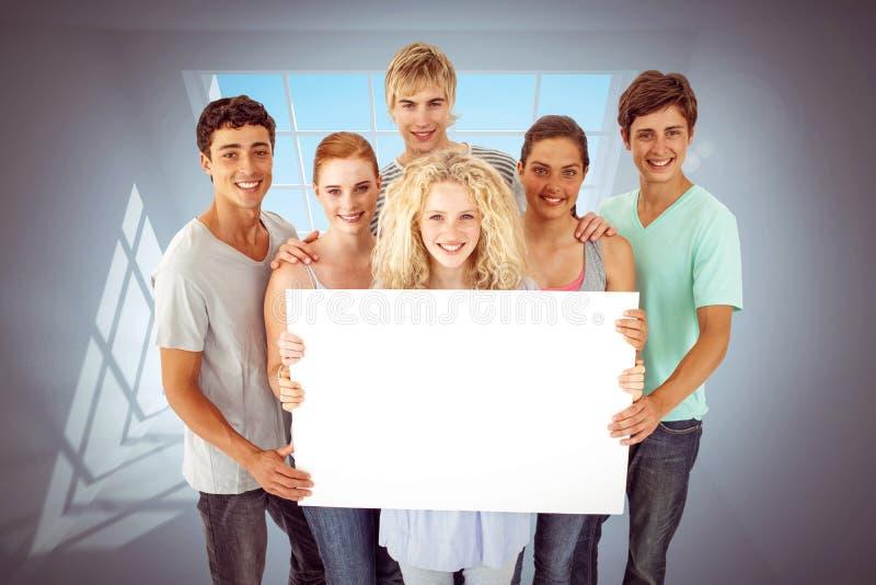 Sammansatt bild av gruppen av tonåringar som rymmer ett tomt kort fotografering för bildbyråer