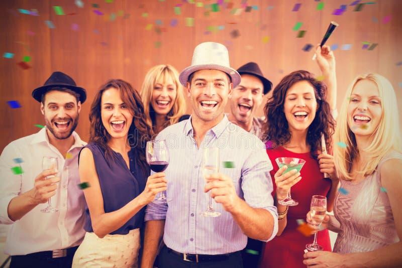 Sammansatt bild av gruppen av vänner som har gyckel, medan stå med drinkar royaltyfri foto