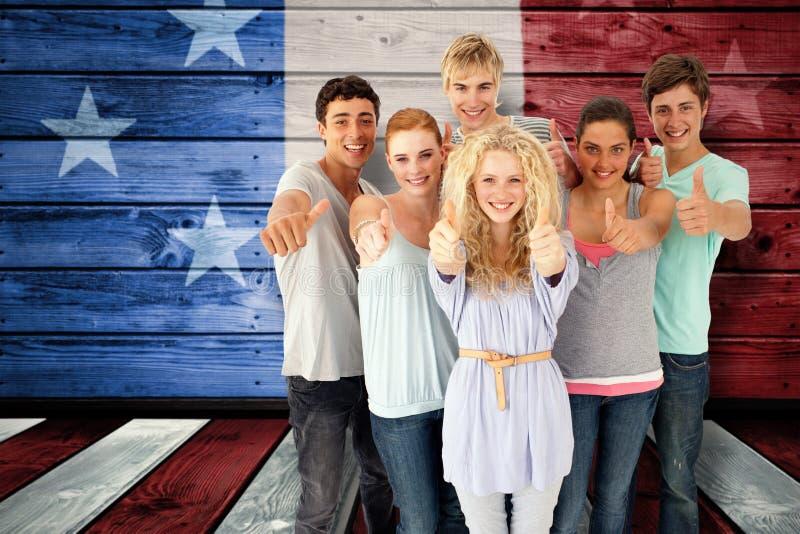 Sammansatt bild av gruppen av tonåringar som framme står av kameran med tummar upp arkivfoto