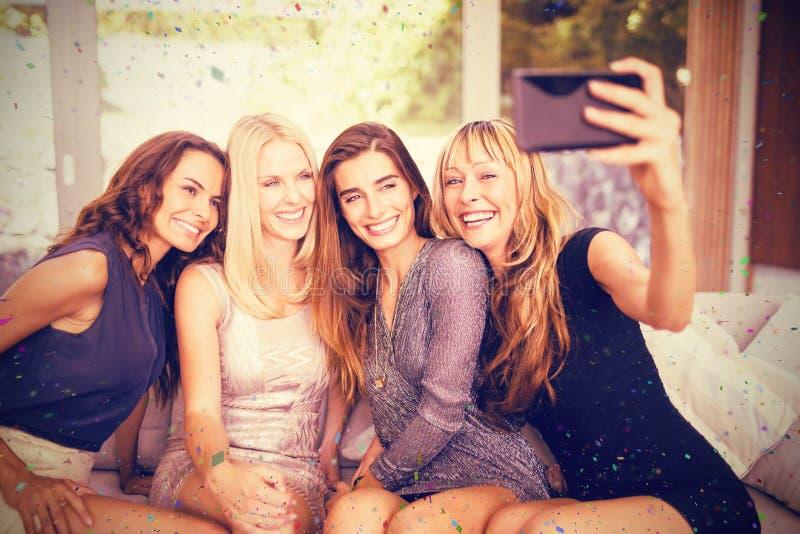 Sammansatt bild av härliga kvinnor som tar selfie med mobiltelefonen royaltyfri bild