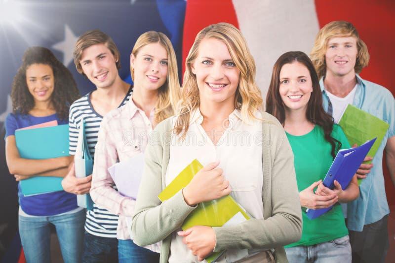 Sammansatt bild av högskolestudenter som rymmer mappar på högskolan royaltyfria foton