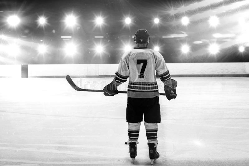 Sammansatt bild av hockeyspelaren med anseende för hockeypinne på isbana royaltyfri foto