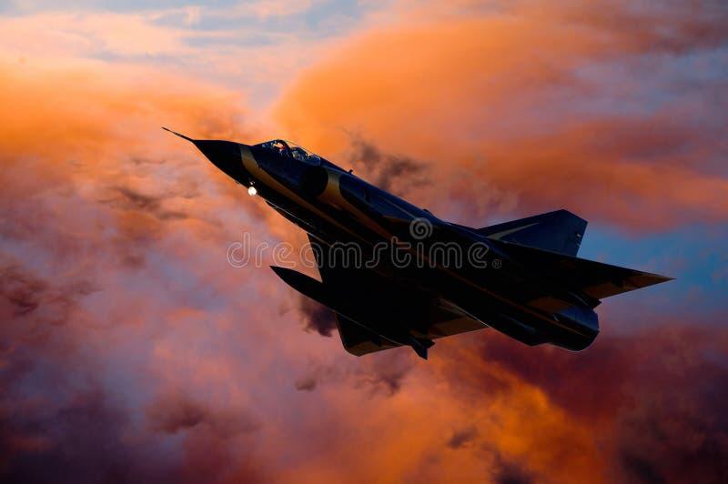 Sammansatt bild av jetplan för jaktflygplan, silhuett mot orangefärgade moln fotografering för bildbyråer