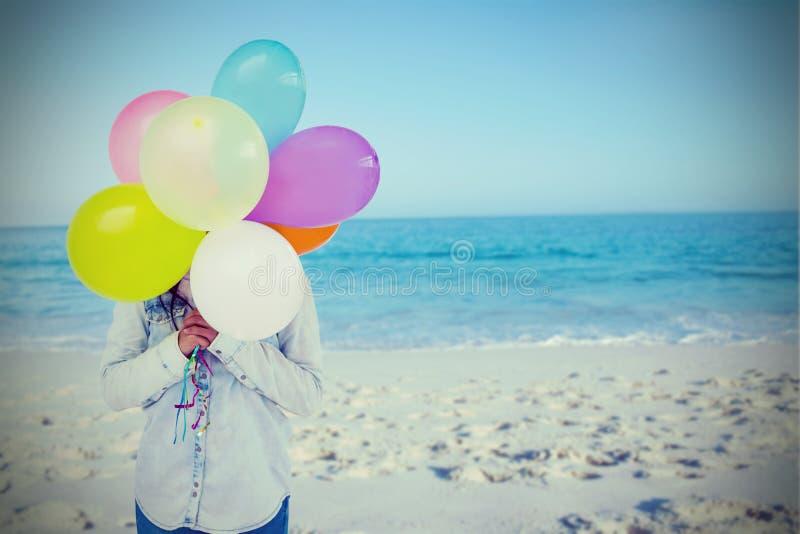 Sammansatt bild av kvinnan som döljer hennes framsida med gruppen av färgrika ballonger arkivbilder