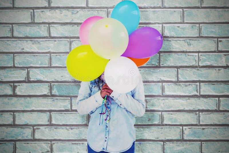 Sammansatt bild av kvinnan som döljer hennes framsida med gruppen av färgrika ballonger royaltyfria bilder