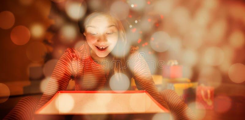 Sammansatt bild av lilla flickan som öppnar en glödande julgåva arkivbilder