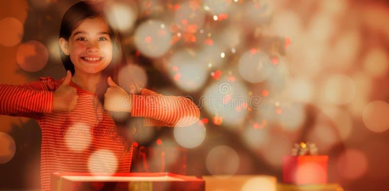 Sammansatt bild av lilla flickan som öppnar en glödande julgåva arkivbild