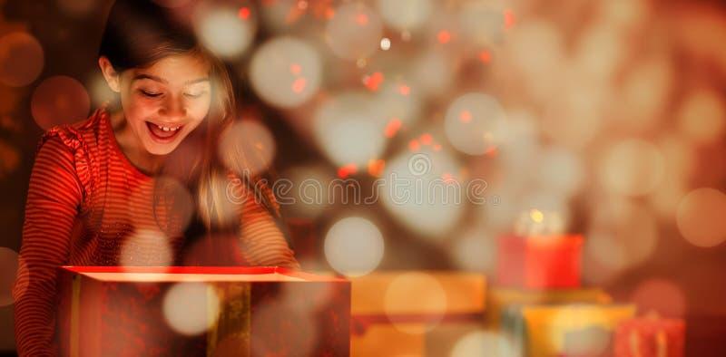 Sammansatt bild av lilla flickan som öppnar en glödande julgåva royaltyfri fotografi