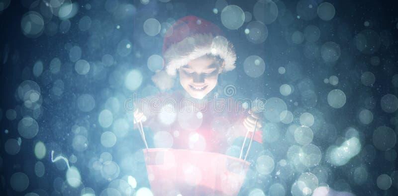 Sammansatt bild av lilla flickan som öppnar en magisk julgåva arkivbild