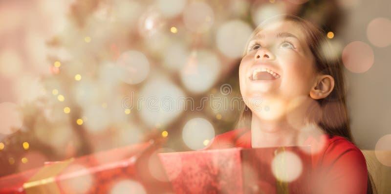 Sammansatt bild av lilla flickan som öppnar en magisk julgåva royaltyfria bilder