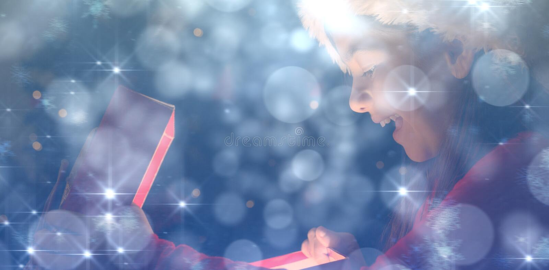 Sammansatt bild av lilla flickan som öppnar en magisk julgåva arkivfoton