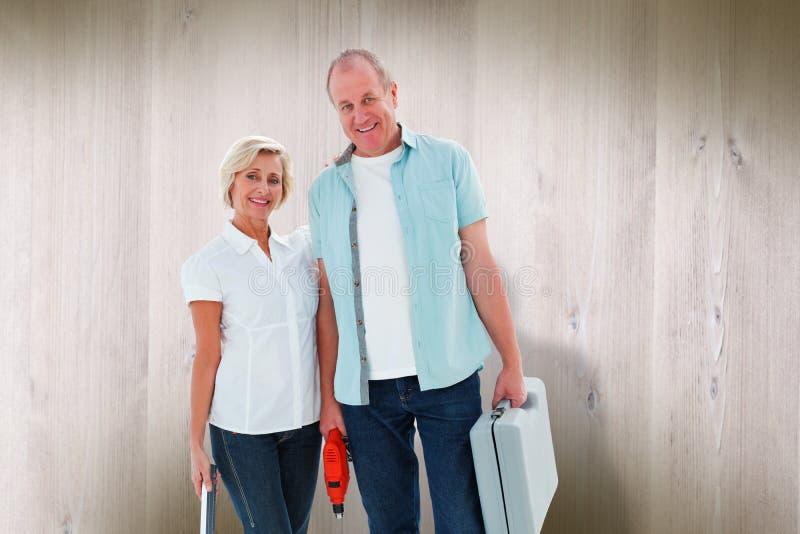 Sammansatt bild av lyckliga äldre par som rymmer diy hjälpmedel arkivfoto