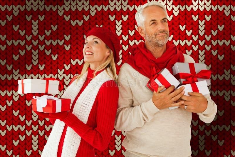 Sammansatt bild av lyckliga festliga par med gåvor arkivbild