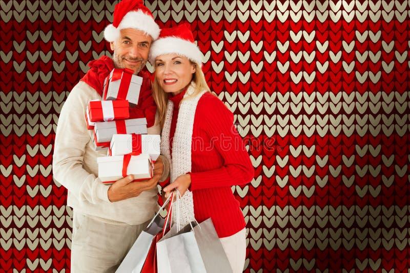 Sammansatt bild av lyckliga festliga par med gåvor och påsar royaltyfri bild