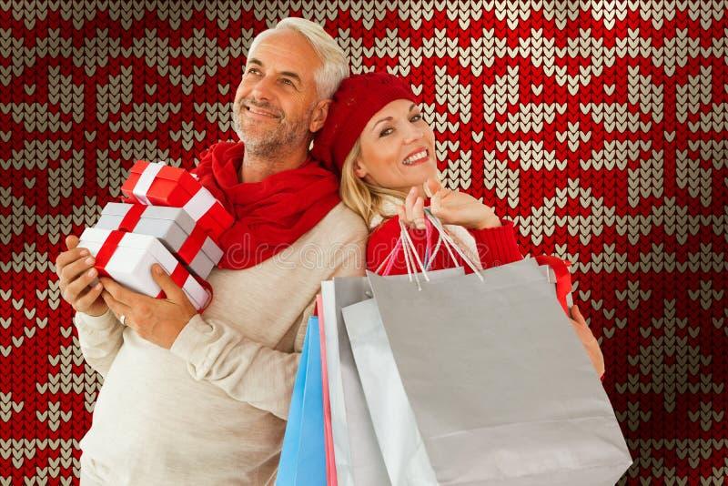 Sammansatt bild av lyckliga festliga par med gåvor och påsar royaltyfria foton